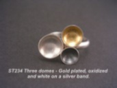 Silver ring with 3 graduated domes, gold, black and white.